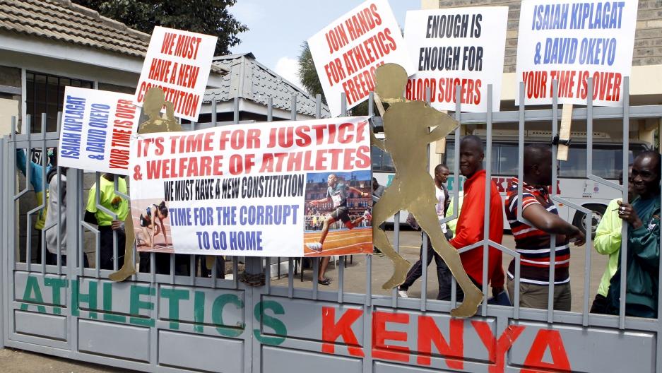 Protesting Kenyan athletes place placards behind closed gates at Riadha  House the Athletic Kenya (AK
