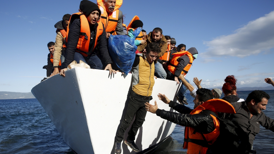 Refugees and migrants jump off a boat as they arrive on the Greek island of Lesbos, November 26, 2015.