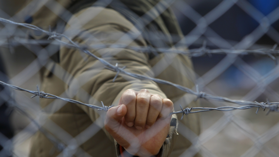 A migrant holds a barbed wire fence at the Macedonian-Greek border, near Gevgelija, Macedonia, November 29, 2015.