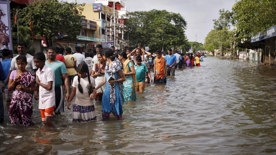 Residents wade through a flooded street as they evacuate their homes in Chennai, in the southern state of Tamil Nadu, India, December 3, 2015.