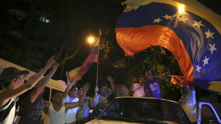 Supporters of the opposition Democratic Unity coalition wave a Venezuelan national flag from a car while they celebrate their victory on a street in Caracas December 7, 2015.