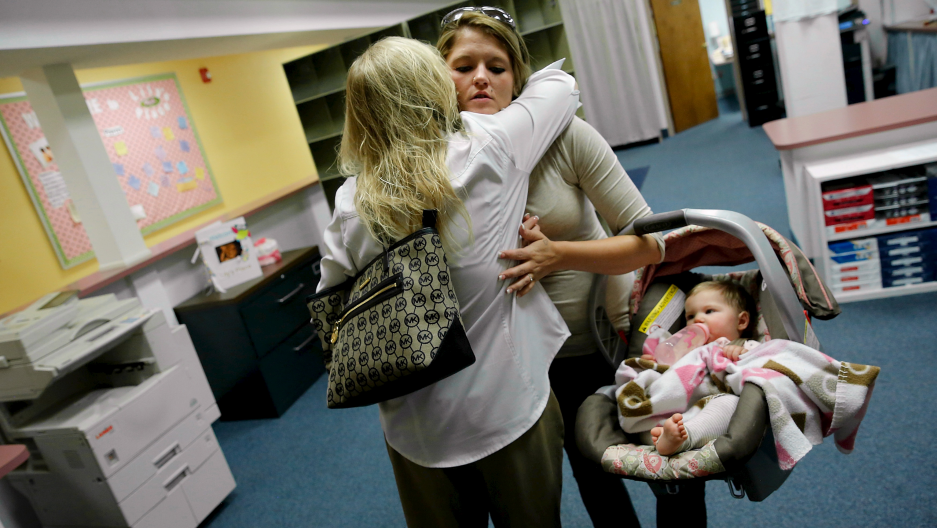 Katy Yeager Gooding hugs her social worker Angela Davis on a visit with her baby Kennedy Gooding to Lily's Place, a treatment center for opioid-dependent newborns in Huntington, West Virginia.