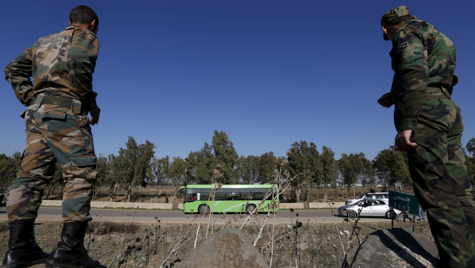 Syrian Army forces look on as buses leave district of Waer during a truce between the government and rebels, in Homs, Syria.