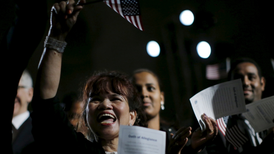 People celebrate as they become U.S. citizens during a naturalization ceremony at the National Archives Museum in Washington.