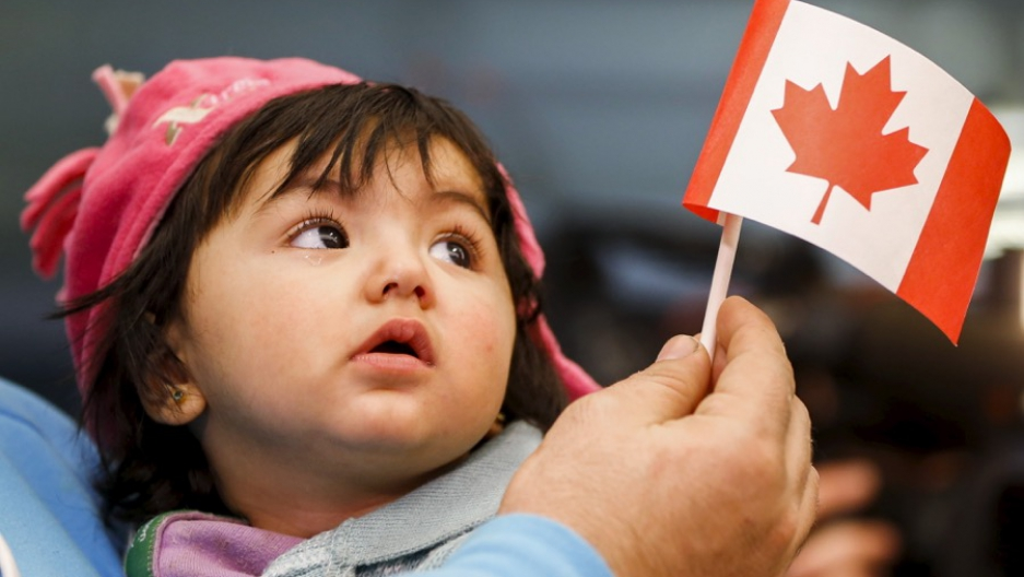 A young Syrian refugee looks up as her father holds her and a Canadian flag at the as they arrive at Pearson Toronto International Airport in Mississauga, Ontario, Dec. 18, 2015.