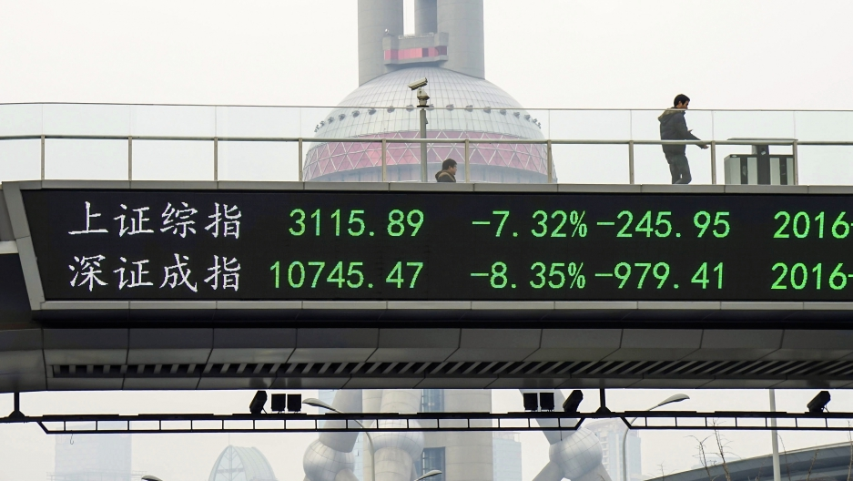 A man stands next to an electronic board in Shanghai showing the benchmark stock indices for Shanghai and Shenzhen, after the new circuit breaker mechanism suspended Thursday's stock trading on the market in Shanghai, China, on January 7, 2016.