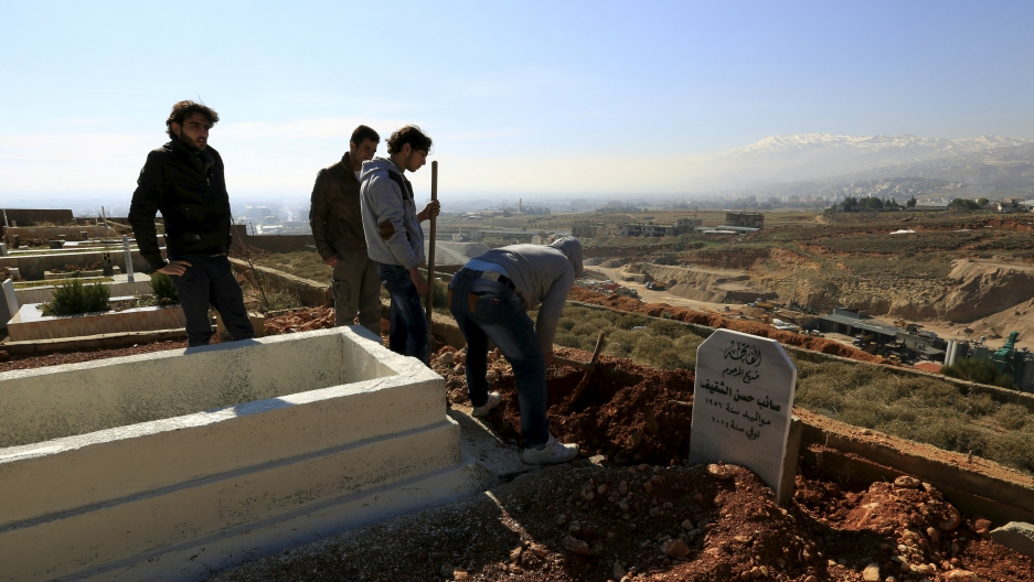 Men dig graves inside a graveyard for Syrian refugees in the village of Taalabaya, Bekaa Valley, Lebanon, Jan. 10, 2016.