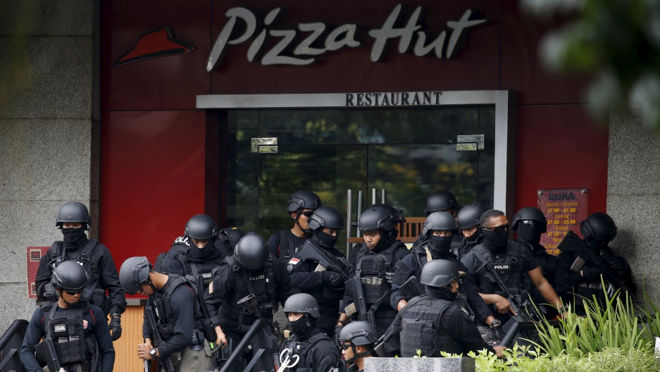 Police gather near the scene of gun and bomb attacks on western targets in Jakarta. The massive security response killed the assailants before they could do much damage.