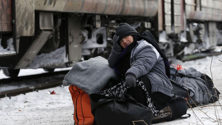 A migrant sits on her bags while waiting for a train in Presevo, Serbia.