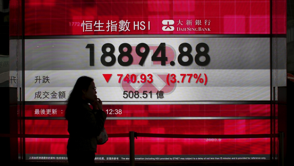 A woman talking on a mobile phone walks past a panel displaying the midday Hang Seng Index in Hong Kong, China January 20, 2016.