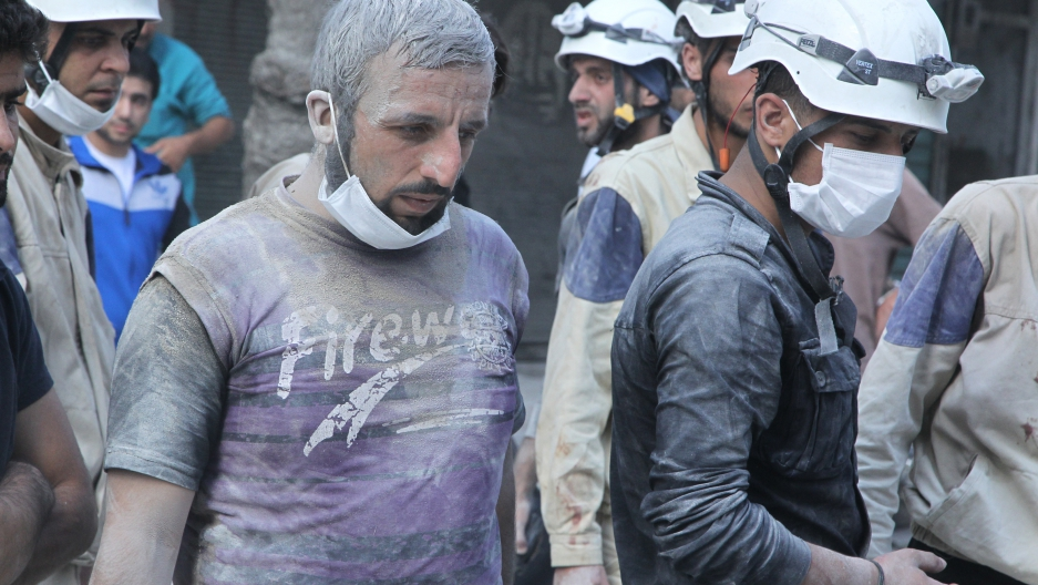 White Helmet volunteers search for survivors at a site reportedly hit with a barrel bomb in the Al-Shaar neighborhood of Aleppo, Syria, on September 17, 2015.