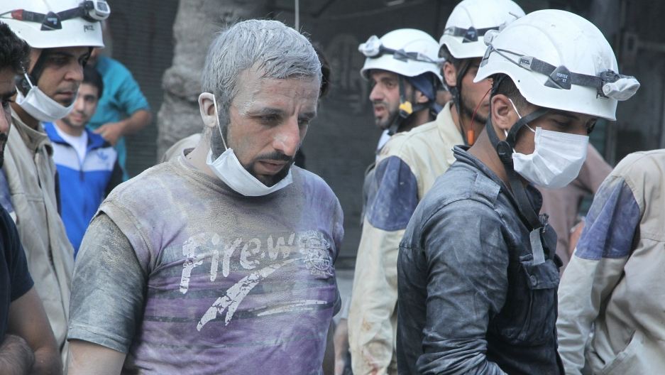 "Residents and members of the Syrian Civil Defense, or ""White Helmets,"" look for survivors at a damaged site after what activists said was a barrel bomb dropped by forces loyal to Syria's President Bashar al-Assad in the Al-Shaar neighborhood of Aleppo, Sy"