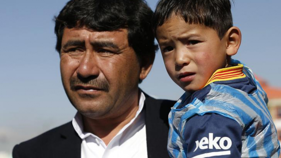 Five year-old Murtaza Ahmadi wears a shirt of Barcelona's star Lionel Messi as his father talks to the media at the Afghan Football Federation headquarters in Kabul, Afghanistan February 2, 2016.