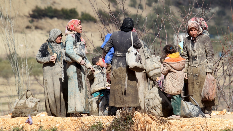 Internally displaced people, wait as they are stuck in the town of Khirbet Al-Joz, in Latakia countryside, waiting to get permission to cross into Turkey near the Syrian-Turkish border, Syria, February 7, 2016.