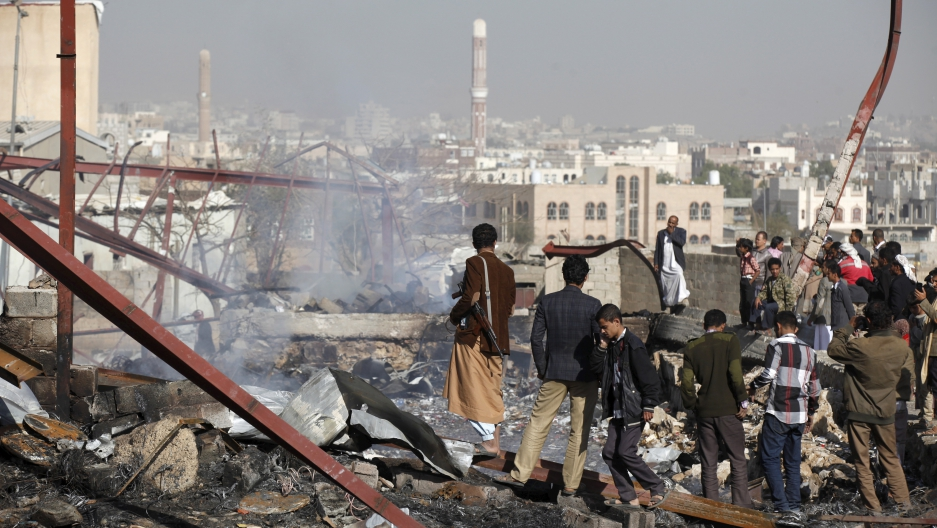 People stand on the rubble of an electronics warehouse store after a Saudi-led air strike destroyed it in Yemen's capital Sanaa