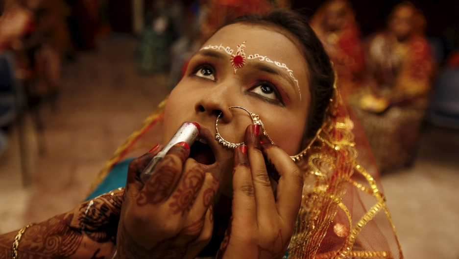 A bride gets her makeup done before her marriage ceremony.