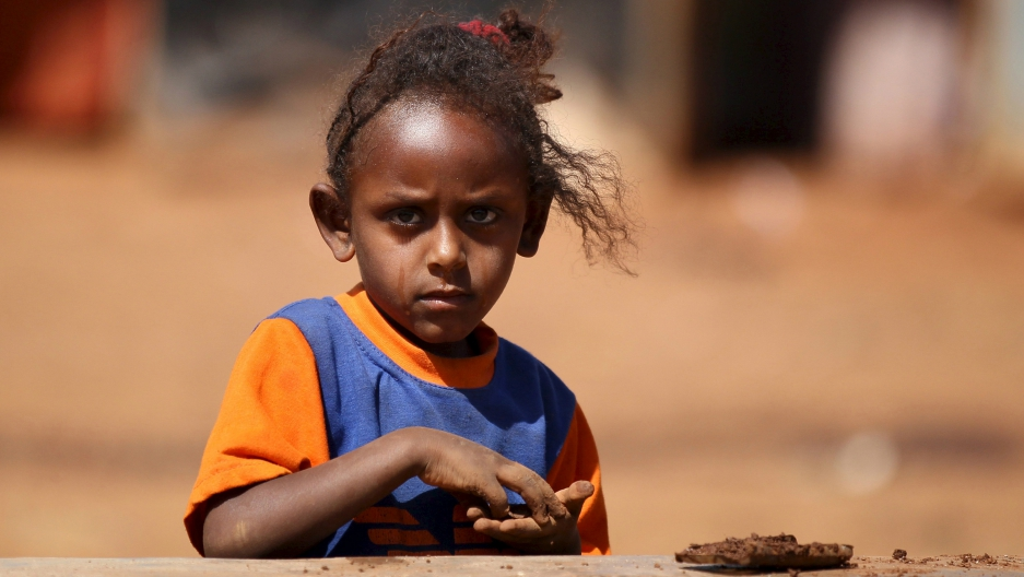 An Eritrean refugee girl plays with clay in front of a shelter in Mai-Aini refugee camp near in the Tigray region of Ethiopia, Feb. 10, 2016.