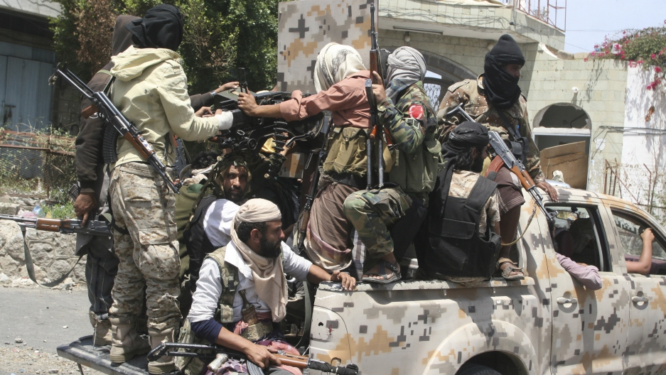 Pro-government fighters ride on the back of a truck in Yemen's southwestern city of Taiz