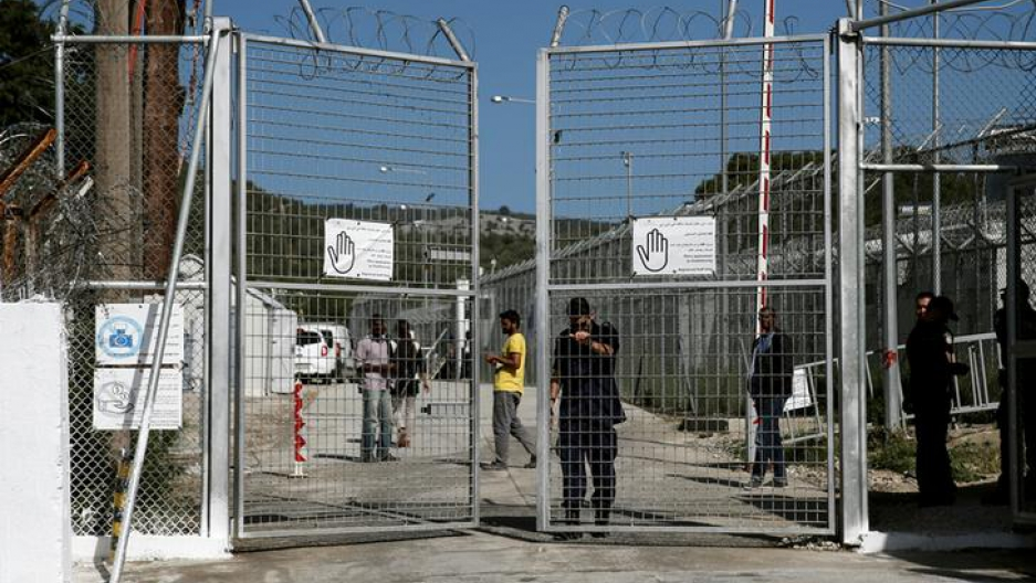 A police officer closes the gate of the Moria holding centre for refugees and migrants, which Pope Francis will visit on April 16 on the Greek island of Lesbos.