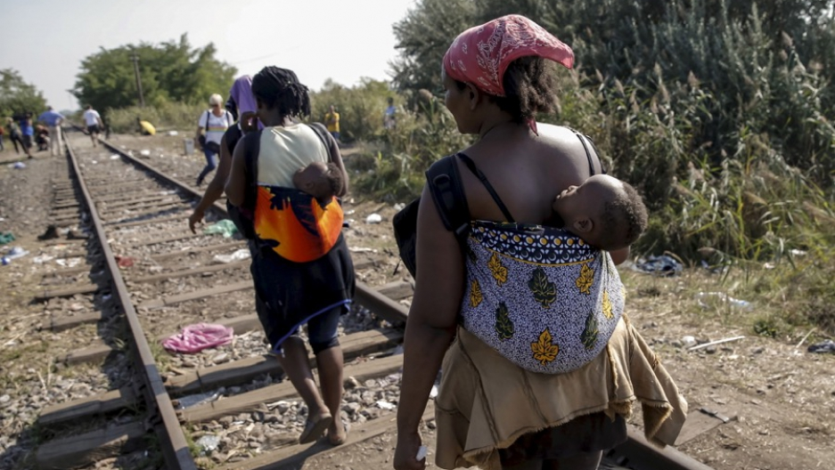 Migrants, hoping to cross into Hungary, walk with babies on their backs along a railway track outside the village of Horgos in Serbia, toward the border it shares with Hungary, on Aug. 31, 2015.