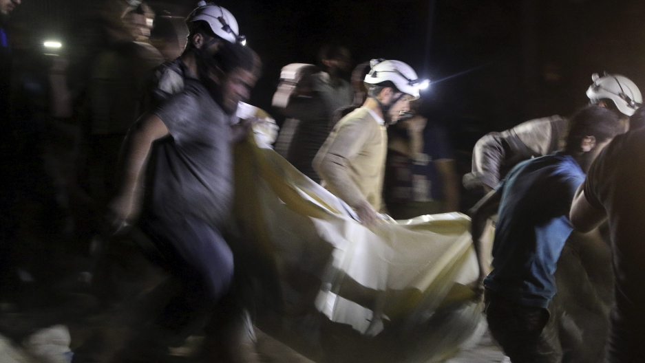 Civil defense members carry a casualty after an airstrike in the rebel held area of al-Sukari in Aleppo.