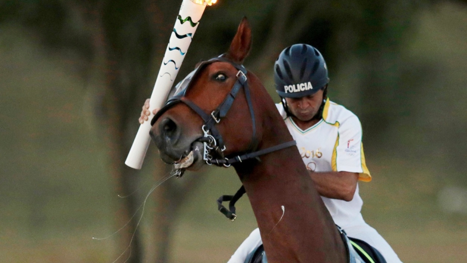 Brazil's Jose Batista holds the Olympic torch as he rides his horse during the torch relay in Brasilia on May 3.