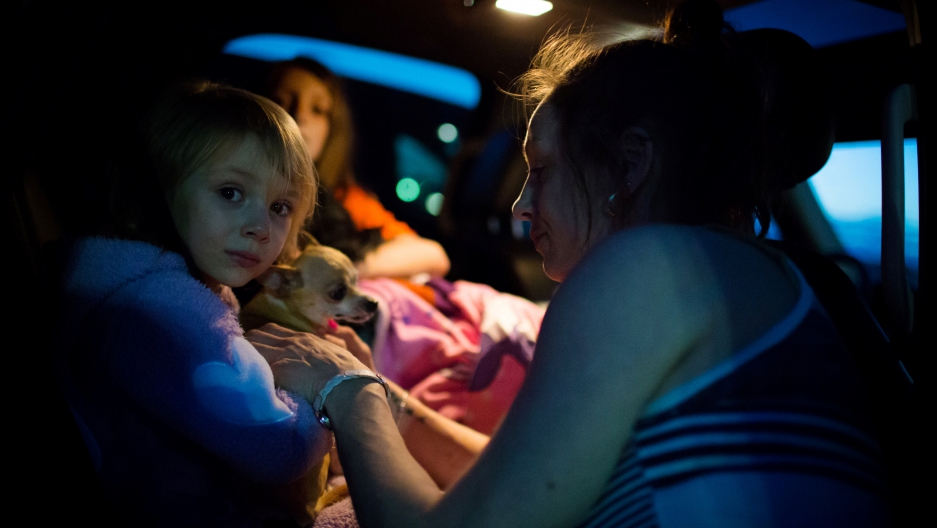 Fort McMurray resident Crystal Maltais buckles in her daughter, Mckennah Stapley, as they prepare to leave Conklin, Alberta, for Lac La Biche after evacuating their home in Fort McMurray on Tuesday May 3, 2016.