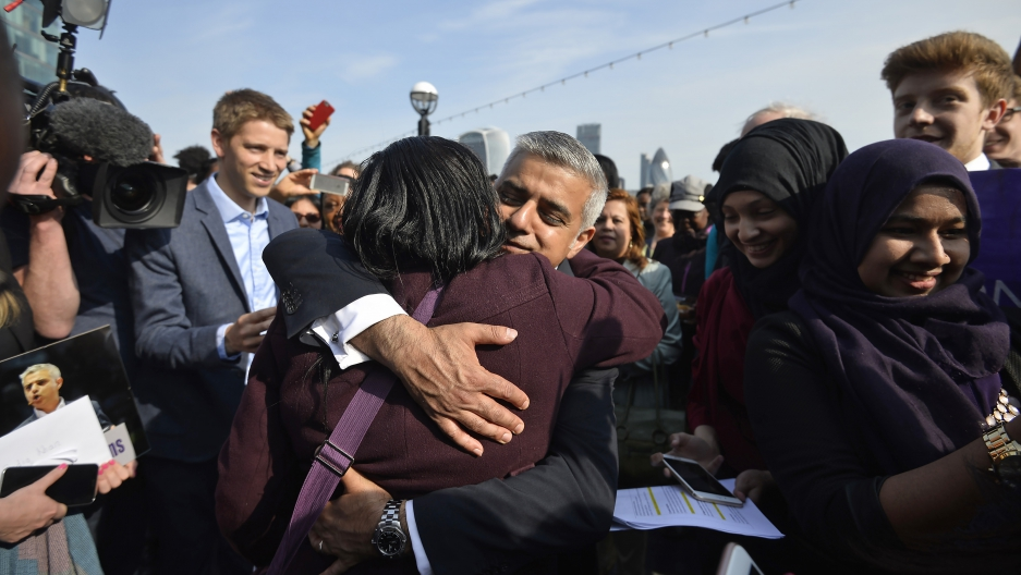Britain's newly elected mayor Sadiq Khan is embraced by a supporter as he arrives for his first day at work at City Hall in London, Britain May 9, 2016.
