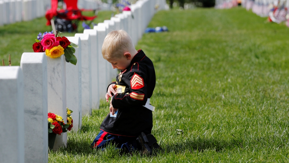 Christian Jacobs touches a photograph of his U.S. Marine father, Christopher Jacobs, while visiting his grave on Memorial Day at Arlington National Cemetery in Washington, U.S., May 30, 2016.