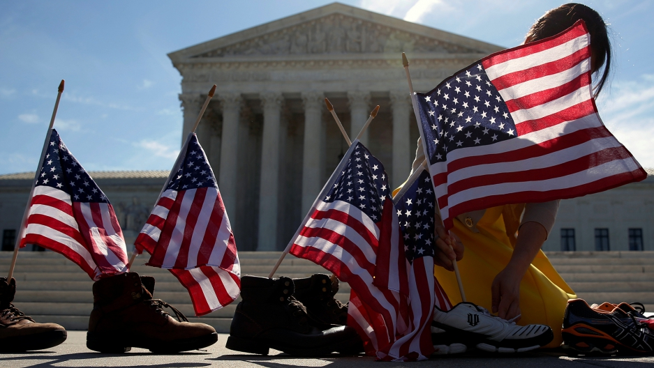 A woman puts flags in a line of shoes on a sunny day in front of Supreme Court building