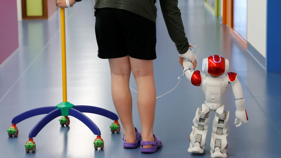 """Belgian Ian Frejean, 11, walks with """"Zora"""" the robot, a humanoid robot designed to entertain patients and to support care providers, at AZ Damiaan hospital in Ostend, Belgium June 16, 2016."""