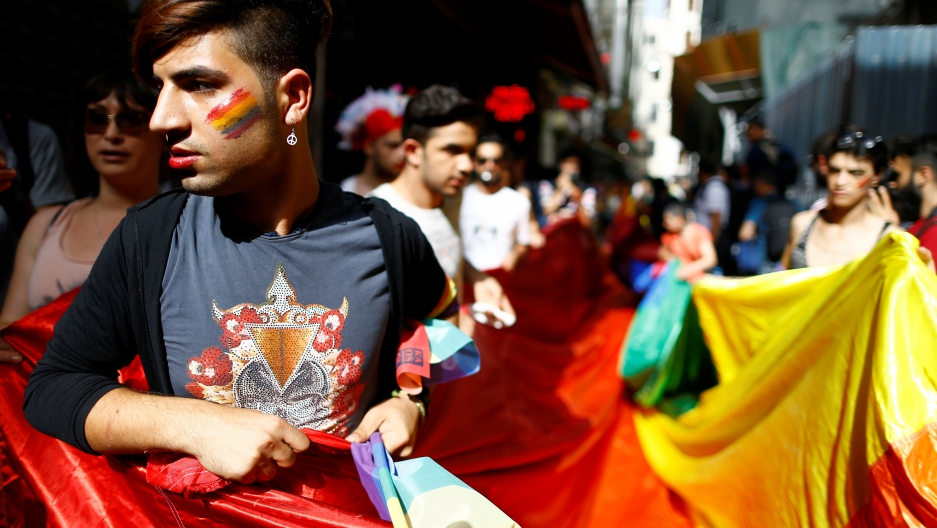 LGBT rights activists hold a rainbow flag during a transgender pride parade which was banned by the governorship, in central Istanbul, Turkey, June 19, 2016