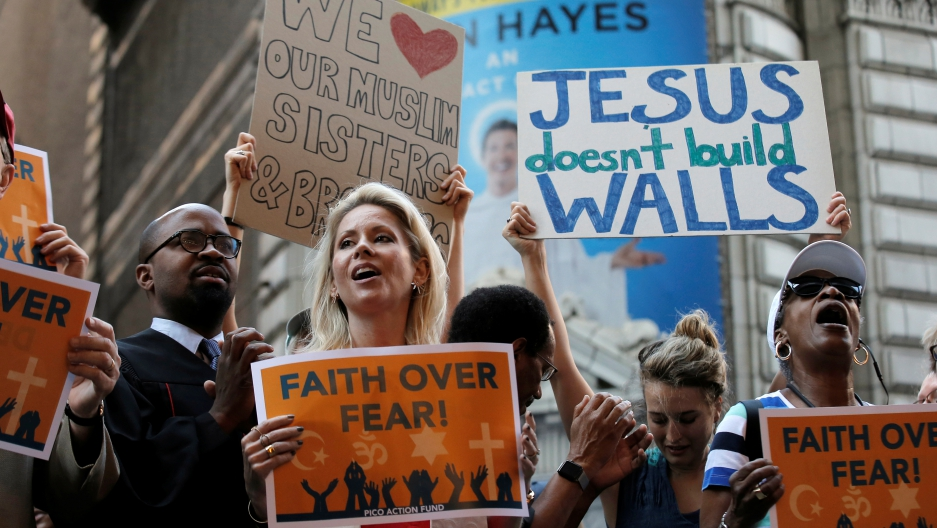 """group of protesters, with signs """"Jesus doesn't build walls"""" and """"Faith over fear"""""""