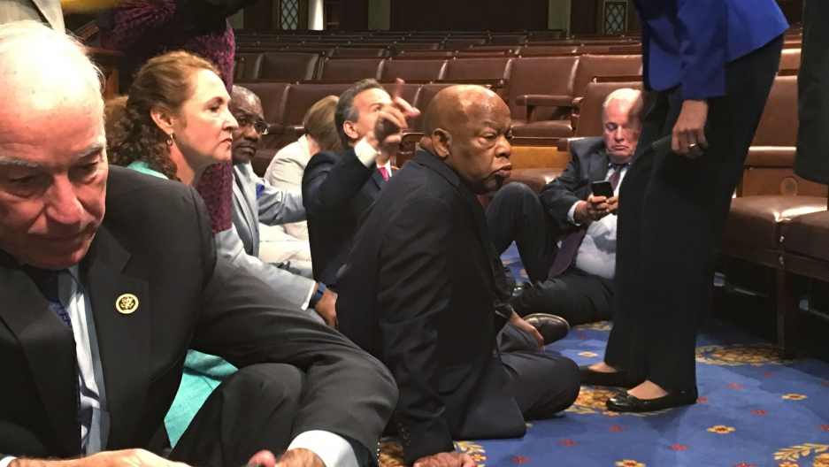 "A photo shot and tweeted from the floor of the House by U.S. House Rep. John Yarmuth shows Democratic members of the U.S. House of Representatives, including Rep. Joe Courtney (L) and Rep. John Lewis (C) staging a sit-in on the House floor ""to demand acti"