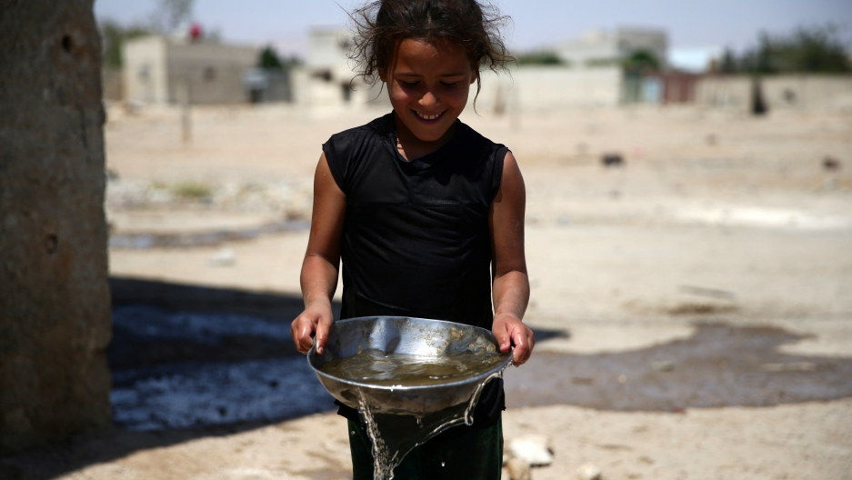 A girl carries a bowl filled with water, in the rebel held besieged town of Douma, eastern Damascus.