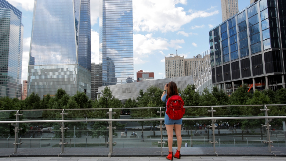 A woman takes a photo from the newly opened Liberty Park above Liberty Street on the World Trade Center site in Manhatten.