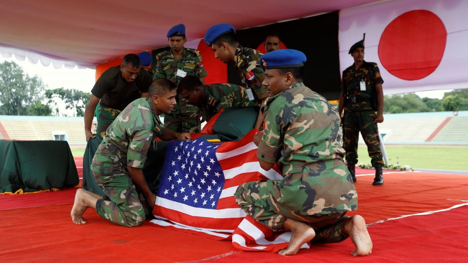 Bangladeshi army personnel place a U.S. flag on a coffin of a victim who was killed in the attack on the Holey Artisan Bakery and the O'Kitchen Restaurant, during a memorial ceremony in Dhaka, Bangladesh, July 4, 2016. REUTERS/Adnan Abidi