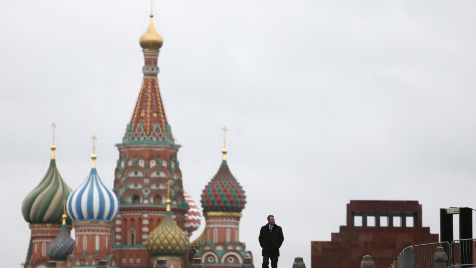 A man walks along Red Square, with the mausoleum of Vladimir Lenin and St. Basil's Cathedral in the background, in central Moscow, Russia.