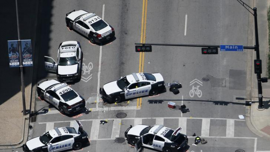 ​Police cars remain parked with the pavement marked by spray paint, in an aerial view of the crime scene of a shooting attack in downtown Dallas.