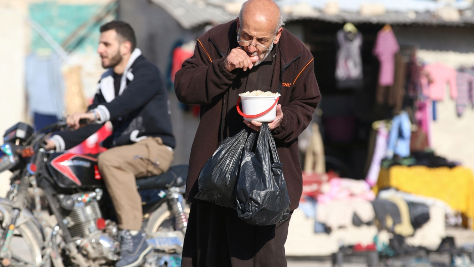 A man eats food distributed as aid in rebel-held eastern Aleppo, Syria, on Nov. 6, 2016.