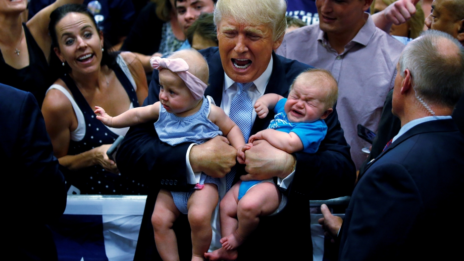 Republican presidential nominee Donald Trump holds babies at a campaign rally in Colorado Springs, Colorado, U.S., July 29, 2016. REUTERS/Carlo Allegri