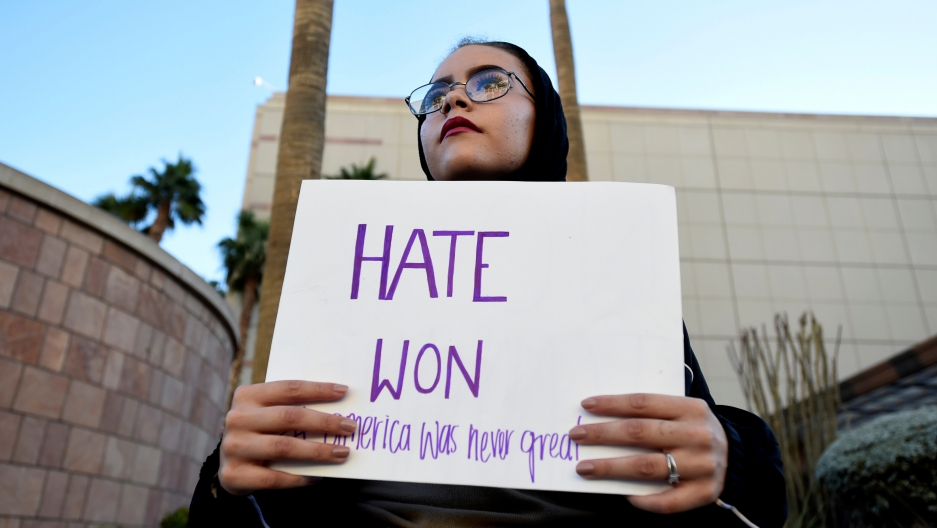 Krystina Robinson of Las Vegas carries a placard in protest against the election of Donald Trump, near the Trump Hotel and Tower in Las Vegas.
