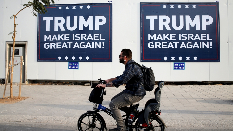 A man cycles past signs bearing the name of U.S. President-elect Republican Donald Trump in Tel Aviv, Israel November 14, 2016.