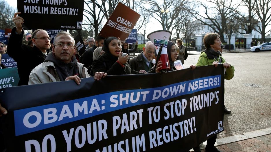"""Protesters march with a sign that says """"Obama: Shut down NSEERS"""""""