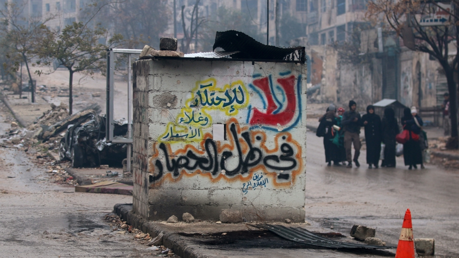 """People carry their belongings as they flee deeper into the remaining rebel-held areas of Aleppo, Syria December 13, 2016. The Arabic words read, """"No to monopolizing commodities and raising prices under the siege."""""""