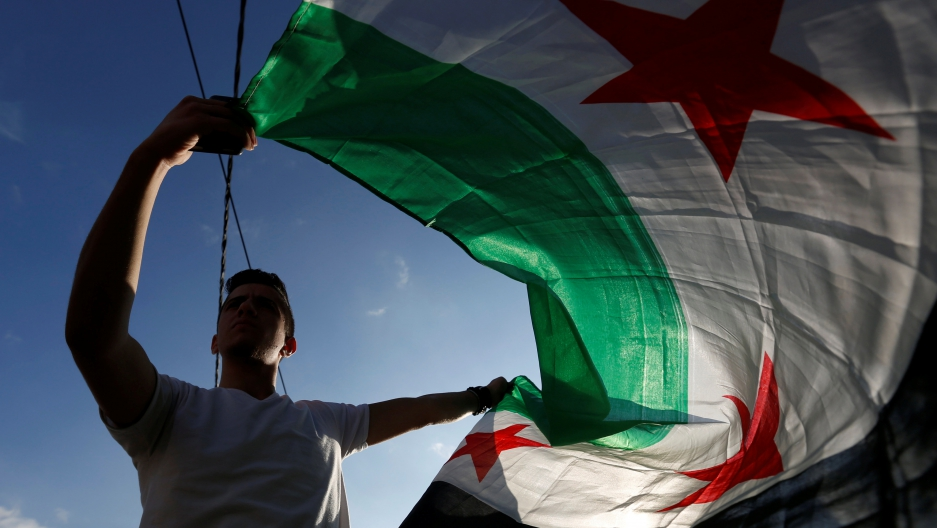 A protester holds a Syrian opposition flag during a sit-in against the Syrian regime, in front of the UNDP office in Amman, Jordan.