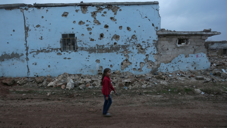 A girl walks near a damaged house in northern Syria, Tuesday. The civil war in Syria is almost six years old.