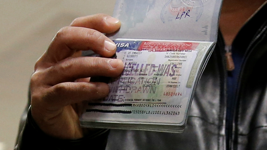 A Yemeni national who was denied entry into the US after President Donald Trump's first immigration and refugee visa ban shows the canceled visa in a passport, at Washington Dulles International Airport in Chantilly, Virginia, Feb. 6, 2017.