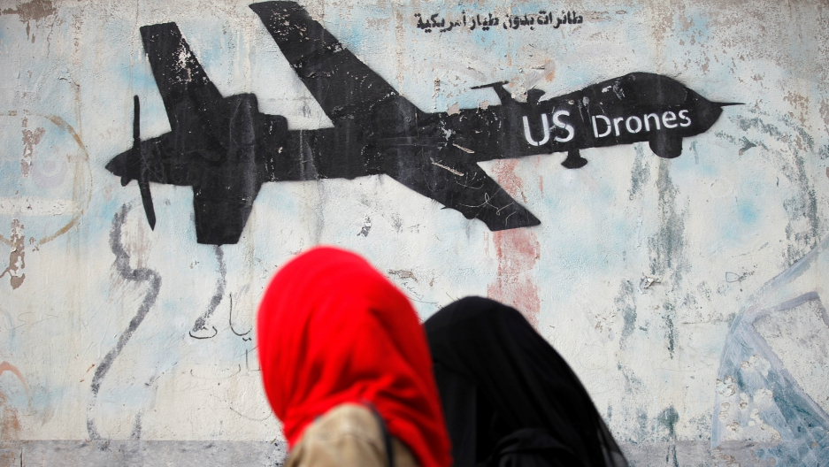 Women walk past graffiti denouncing strikes by US drones in Yemen, painted on a wall in Sanaa, Yemen, Feb. 6, 2017.