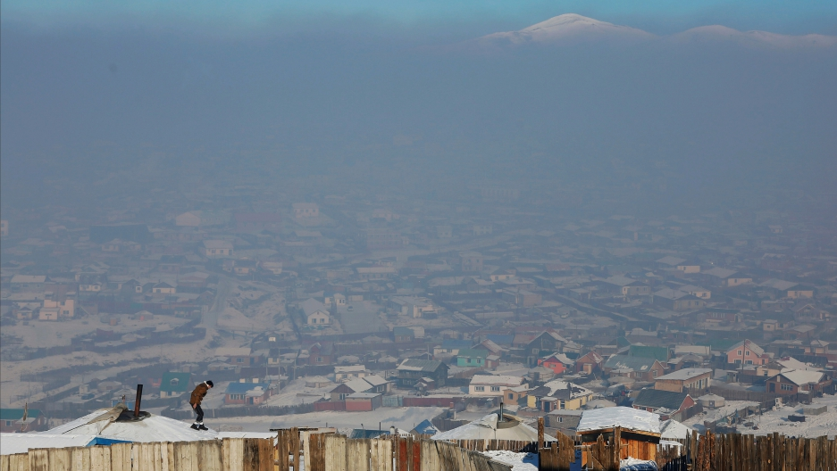 A man walks on the roof of a traditional ger home while fixing the chimney of a coal burning stove on a cold hazy day on the outskirts of Ulaanbaatar, Mongolia.
